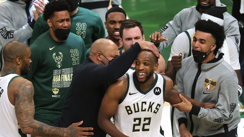 Khris Middleton is congratulated by Bucks team-mates during the second half