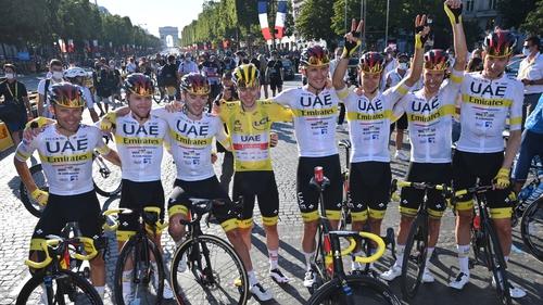 Tadej Pogacar celebrates on the Champs Elysees with his UAE Team Emirates colleagues