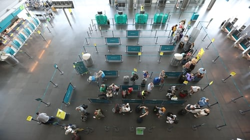 Passengers queuing at check-in desks to show their Covid vaccine certs at Dublin Airport