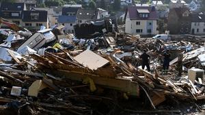 Workers walk amid debris in Kreuzberg, district of Altenahr, Rhineland-Palatinate