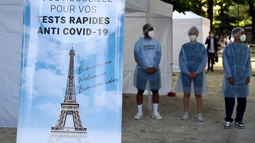 Health workers stands near an antigenic test area outside the Eiffel Tower
