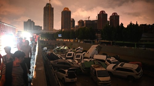 People look at cars stacked on each other at an entrance of a tunnel following the heavy rains