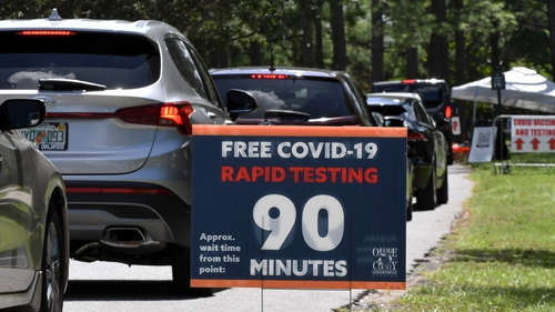 People in cars wait at a Covid-19 testing and vaccination site at Barnett Park, Orlando, Florida