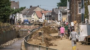 People walk on a muddy street along the river among piles of debris in Swisttal-Odendorf, near Euskirchen, North Rhine-Westphalia