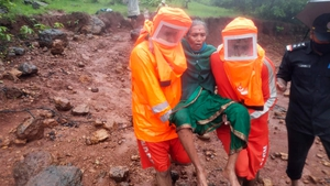National Disaster Response Force rescuers carry a woman to safety in Maharashtra state