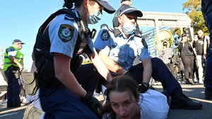 Police officers detain a protestor during a rally in Sydney