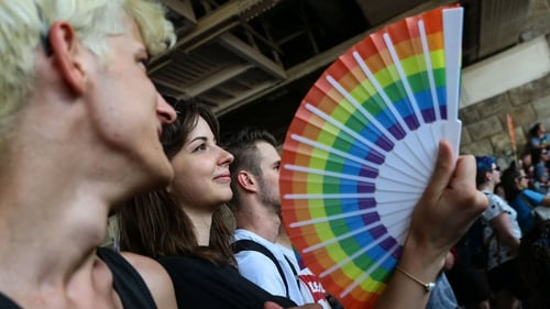 A participant holds a fan with rainbow colours during the LGBTQ Pride Parade in Budapest today