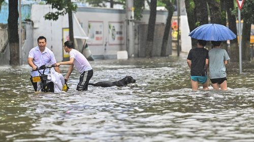 People wade in a flooded street in Ningbo in eastern China's Zhejiang province today