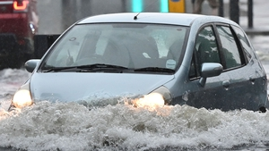 A car is driven through deep water on a flooded road in The Nine Elms district of the city