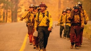 Firefighters walk along a road while working the scene during the Dixie fire in the Prattville community of unincorporated Plumas County