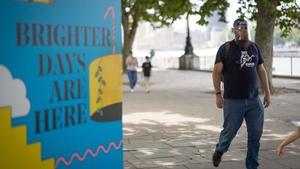 A pedestrian walks past a coraonvirus sign in London