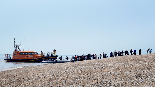 Migrants are watched over by the RNLI as they make their way up the beach in Kent