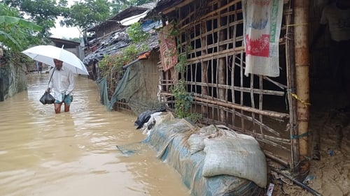 A man walks through flood waters in the camp