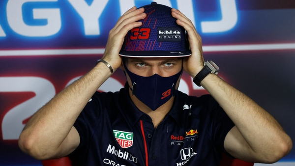 Verstappen adjusts his cap as he addresses a press conference at the Hungaroring