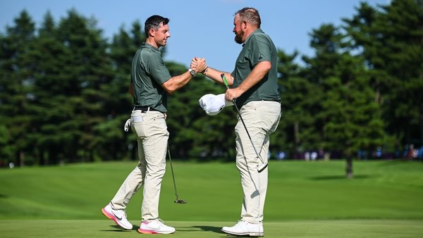 Rory McIlroy (L) and Shane Lowry shake hands after completing their third round together