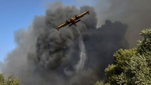 A plane drops water on flames around the town of Labiri, near Patras in Greece