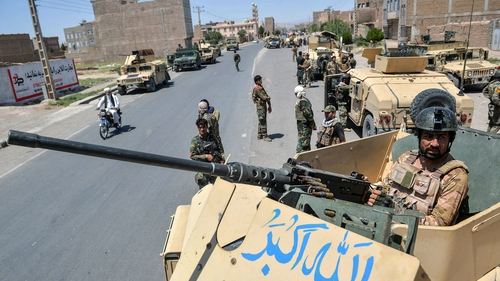 An Afghan army commando stands guard on top of a military vehicle in Enjil district, Herat province, today