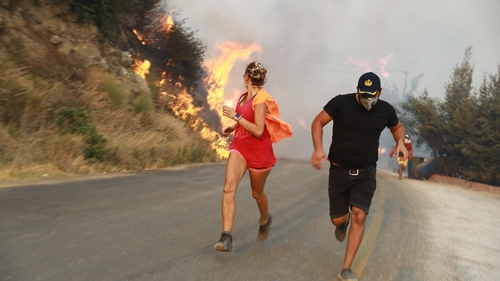 People run away from the fire as ground and aerial extinguishing operations continue in Mugla, Turkey