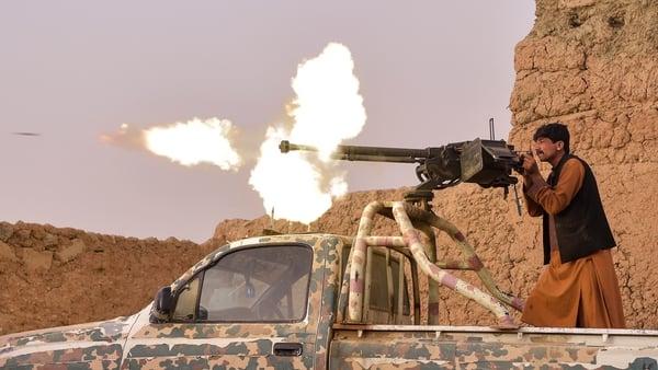 An anti-Taliban militia fighter fires a heavy machine gun in Mukhtar, on the outskirts of Lashkar Gah (File pic)