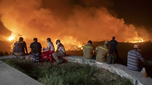 People watch the wildfires as they wait to be evacuated from Evia