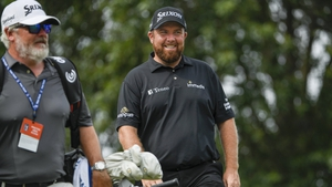Shane Lowry smiles on his way to the 10th tee