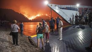 People board a ferry to evacuate the island of Evia, Greece