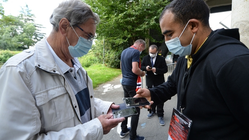 Staff members check supporters' Covid-19 health pass and tickets before the start of the French football match between Stade Rennais Football Club and RC Lens
