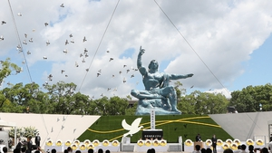 Doves fly during a memorial service for atomic bombing victims at the Nagasaki Peace Park