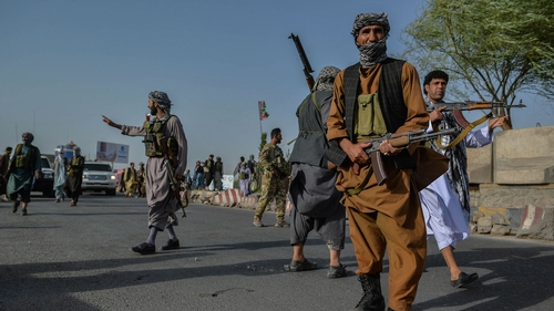 Afghan security personnel stand guard in Enjil district of Herat province