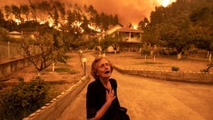 An elderly resident reacts as a wildfire approaches her house in the village of Gouves, on the island of Evia