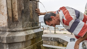 A man refreshes himself in a fountain during a hot summer day in Messina