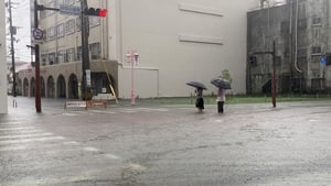 People wade through flooded streets in Saga city