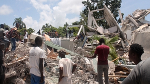 People search through the rubble of what used to be the Manguier Hotel in Les Cayes