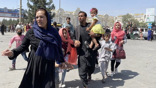 An Afghan family rushes to the Hamid Karzai International Airport as they look to flee the Taliban