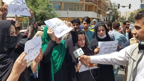 Afghan women, holding placards, gather to demand the protection of women's rights in front of the Presidential Palace in Kabul