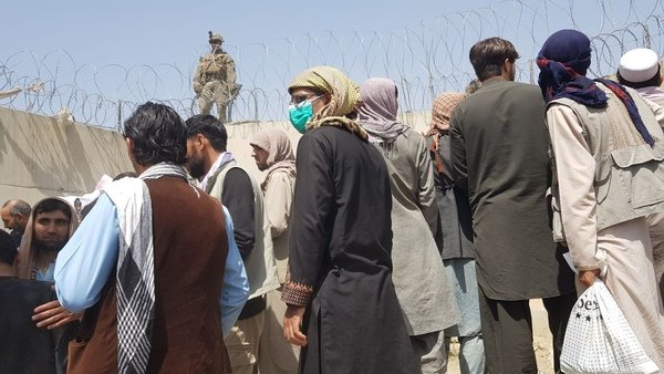 People trying to leave Afghanistan wait near Kabul airport