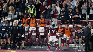 Michail Antonio holds up a cardboard cutout of himself as he celebrates with West Ham fans