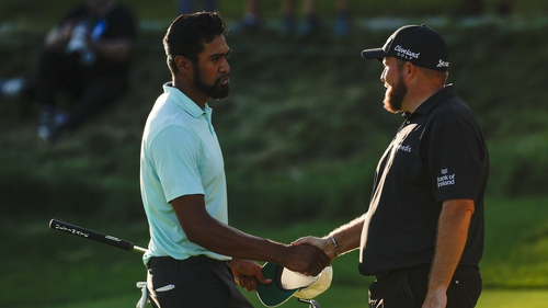 Tony Finau and Shane Lowry shake hands on the 18th green during the final round