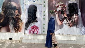 A woman passes by a beauty salon in Kabul, where photos of women have been covered in black pain