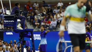 Novak Djokovic points to a rambunctious spectator in the Arthur Ashe Stadium crowd intent on distracting the world number one