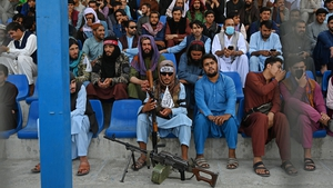 A Taliban fighter keeps watch as spectators watch the Twenty20 cricket trial match being played between two Afghan teams - 'Peace Defenders' and 'Peace Heroes' - at Kabul International Cricket Stadium today