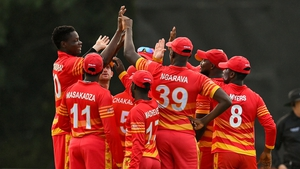 Blessing Muzarabani is mobbed by team-mates after claiming the wicket of Ireland's George Dockrell