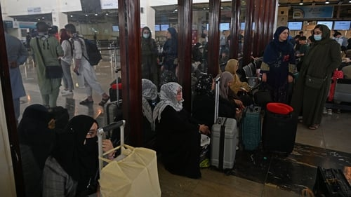 Passengers sit inside the departure terminal at the airport in Kabul