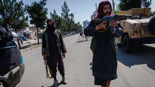 Taliban fighters try to stop the advance of protesters marching through the Dashti-E-Barchi neighbourhood