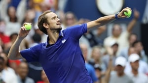 Medvedev throws a tennis ball to fans after clinching victory
