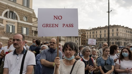 A demonstrator holds up a banner during a demonstration against the 'Green Pass' last weekend