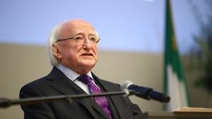 President Higgins stands over church service de...