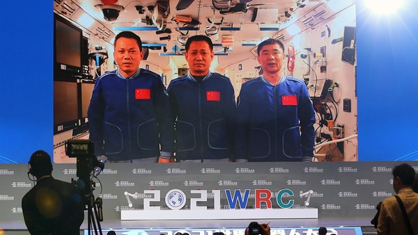 A screen shows Nie Haisheng, Liu Boming and Tang Hongbo speaking on board the Tiangong space station on 10 September