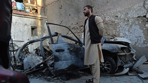 Aimal, brother of Ezmarai Ahmadi, stands next to the wreckage of a vehicle that was damaged in a US drone strike
