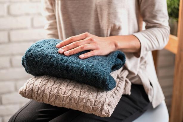 woman holding knitwear